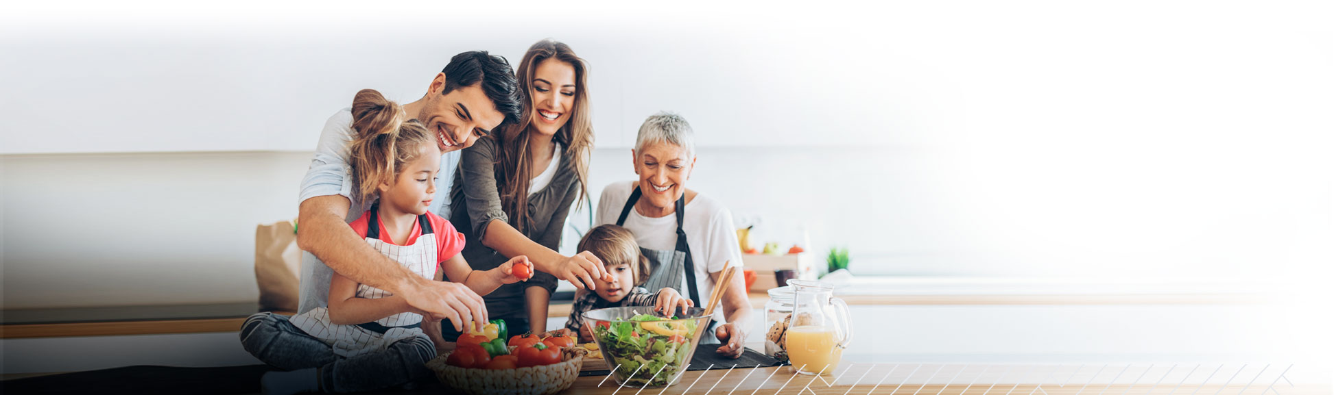 Family in a kitchen holding fruits and vegetables